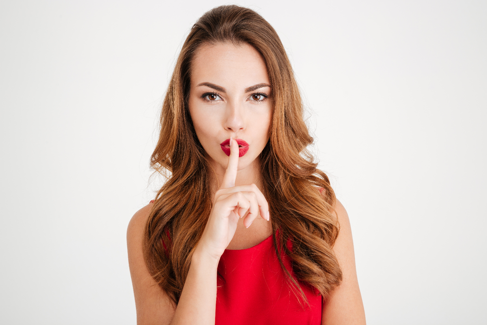 graphicstock-portrait-of-a-young-woman-in-red-dress-showing-silence-gesture-with-finger-over-lips-isolated-on-a-white-background_H_erq1Trhl.png