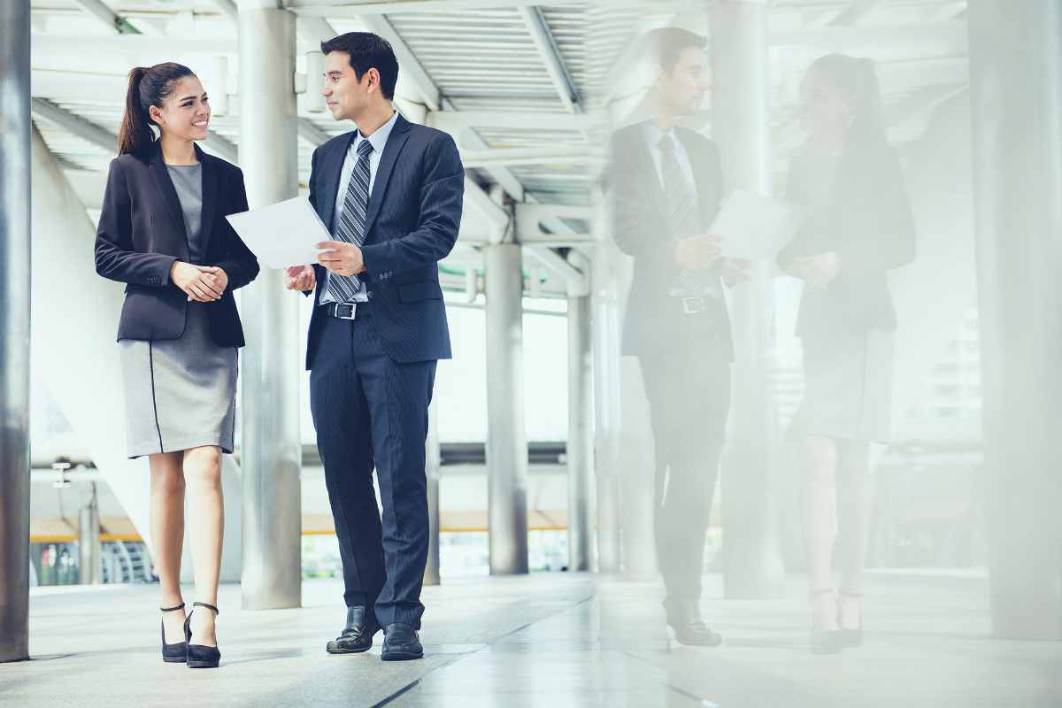 businessman and businesswoman discussing work while walking   Commercial Real Estate Brokerage: How Can It Help You Reach Your Financial Goals   real estate brokerage