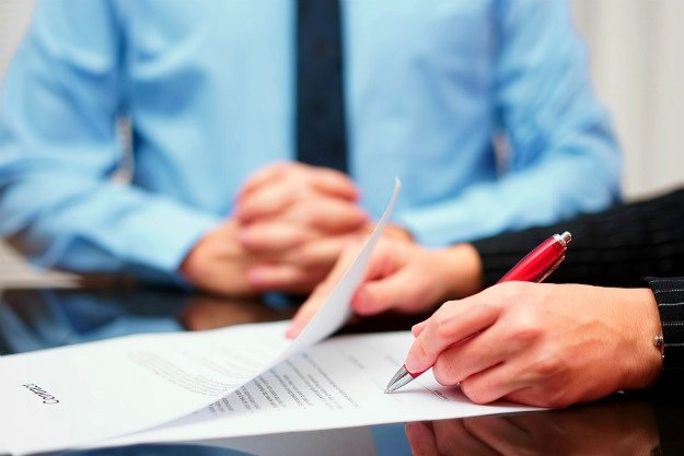 woman signing contract business man background | Commercial Real Estate Sale and Purchase Agreement | Everything You Need To Know | purchase and sale agreement